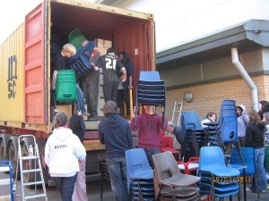 Students of All Saints School loading the first container