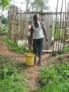 Ibrahim collecting water from the old well at the University